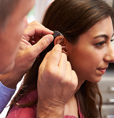 audiologist putting hearing aid on patient