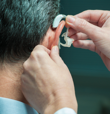 audiologist placing hearing aid on a patient