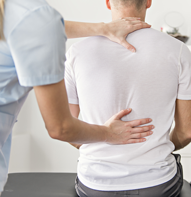 Physical therapist evaluates patients back