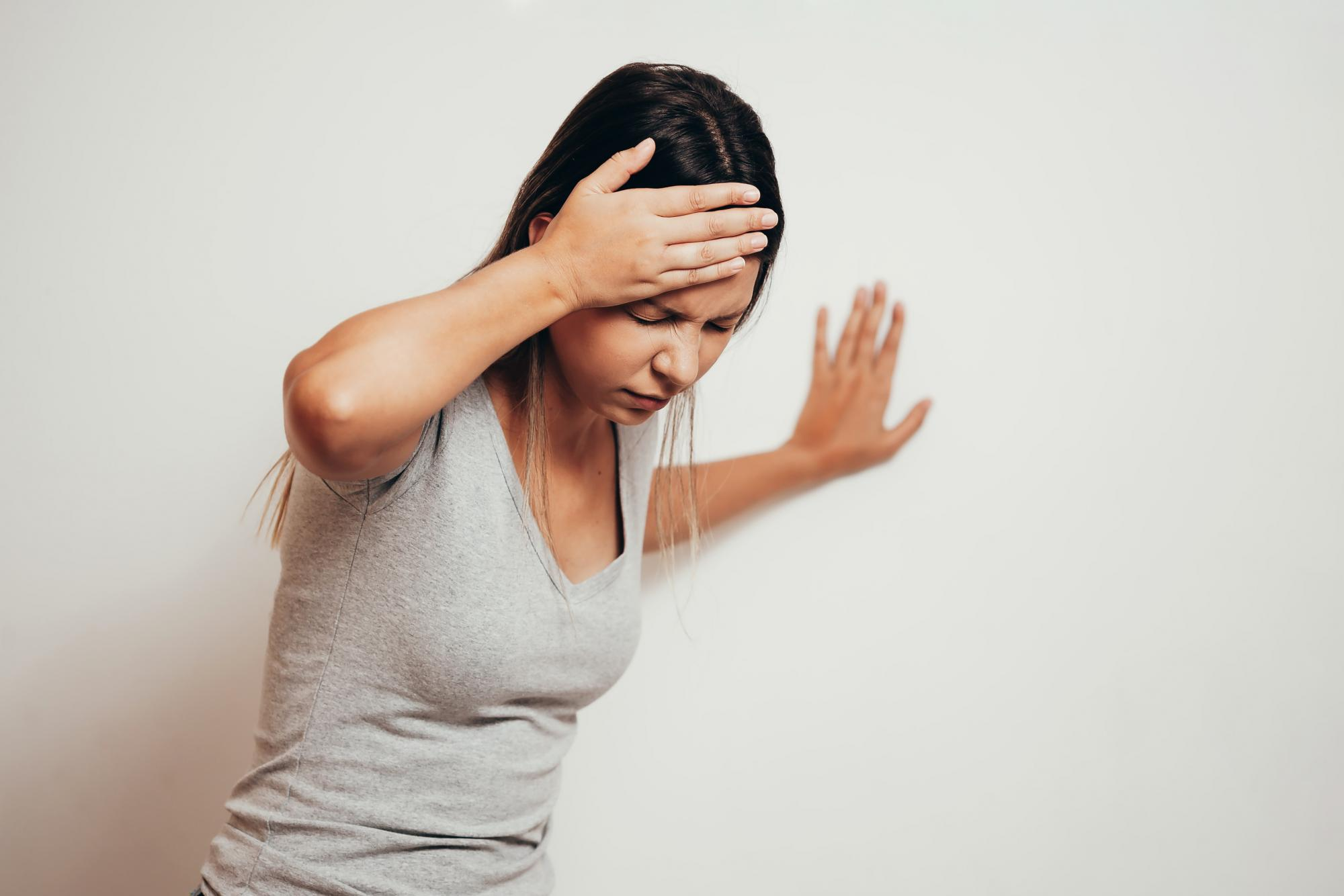 Woman holding her head due to dizziness when standing
