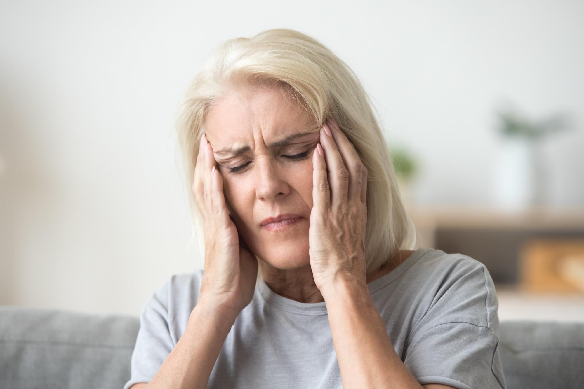 Older woman suffering from dizziness and vertigo