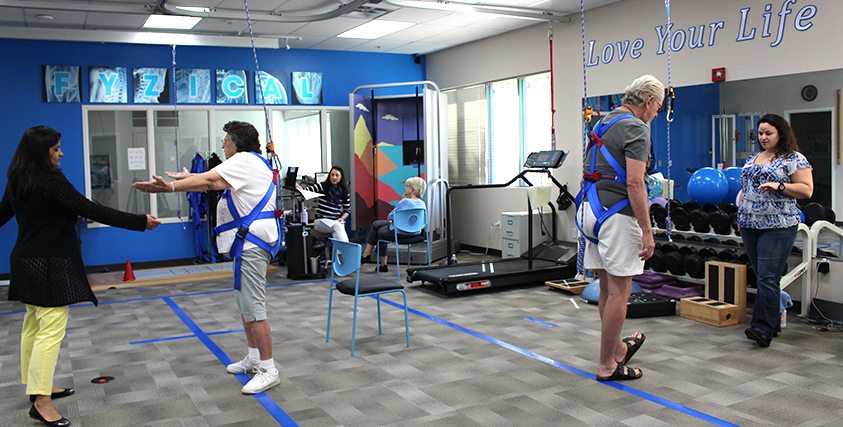 Physical therapists and Physical therapy assistants in the clinic with patients. The patients are doing their exercises while on the harness system